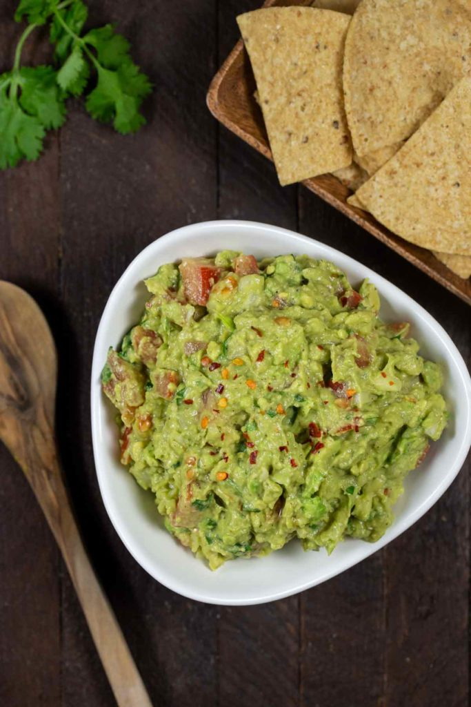 A bird's eye view of a white bowl of guacamole, with tortilla chips and a wooden spoon on the side.