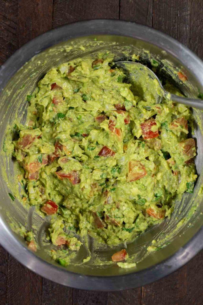 A stainless steel mixing bowl filled with guacamole and a spoon.
