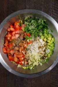 An overhead shot of the ingredients for guacamole added to a stainless steel bowl.