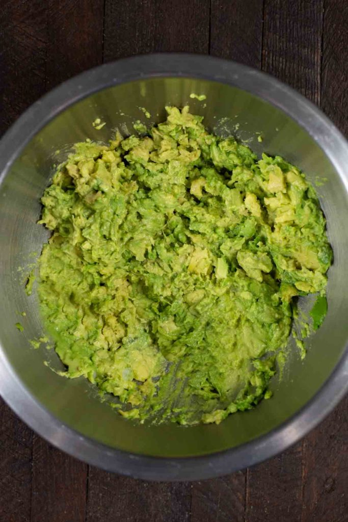 A stainless steel bowl filled with mashed avocado on a wooden background.