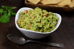 A white bowl of guacamole with a spoon, and some tortilla chips in the background.