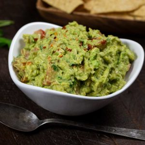 A white bowl of colorful guacamole with a spoon and a plate of tortilla chips in the background.