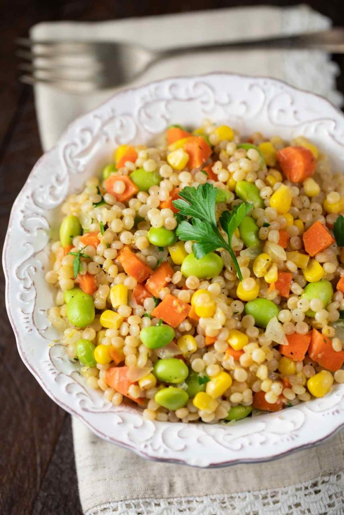 White decorative bowl filled with Israeli couscous with veggies.