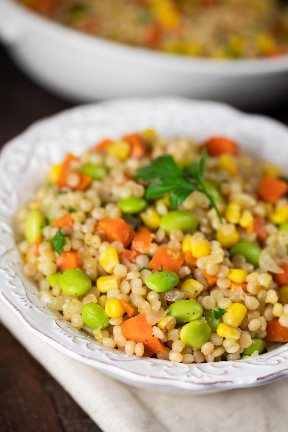 Israeli couscous in a white bowl with edamame, carrots, corn and parsley.
