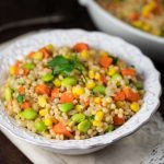 A bowl of israeli pearl couscous with colorful veggies.