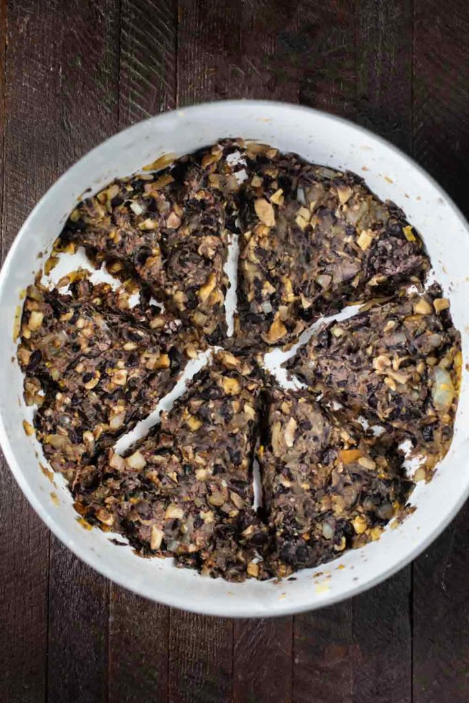 A pan of an onion/mushroom/black bean mix divided into 6 sections.