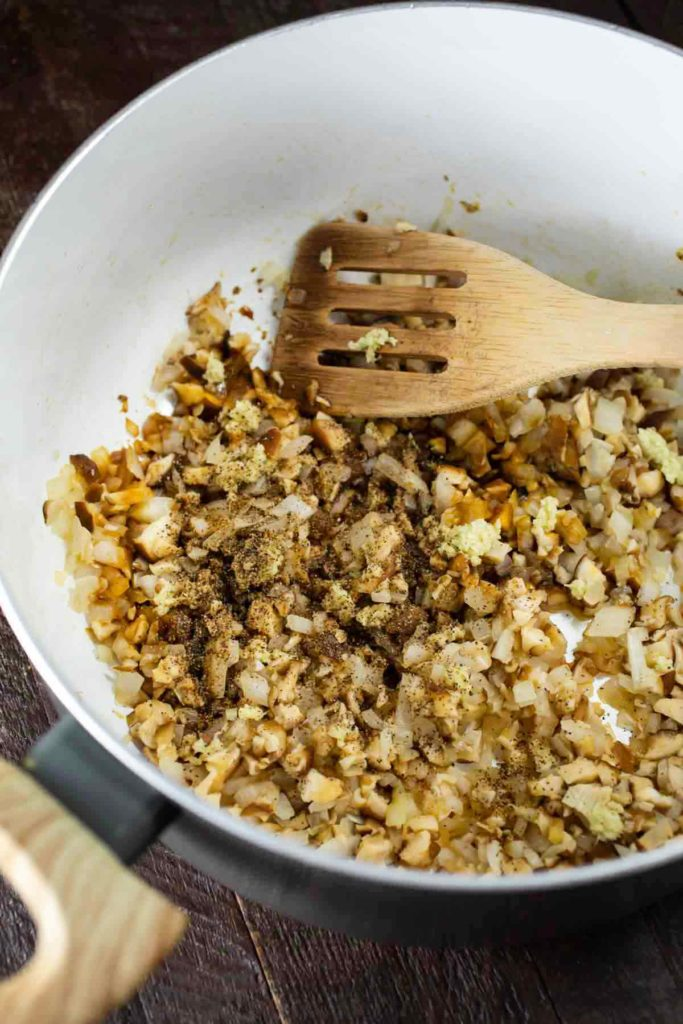 Chopped onions and mushrooms with spices in a skillet.