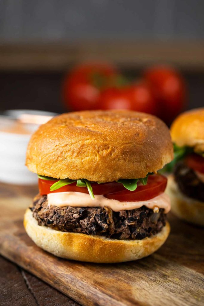 A shiitake black bean burger topped with sliced tomatoes, arugula and a spicy mayo.