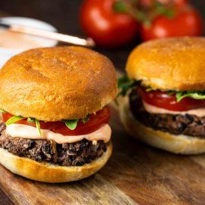 2 Shiitake Black Bean Burgers on a cutting board.