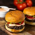 Shiitake burgers with spicy aioli and tomatoes in the background