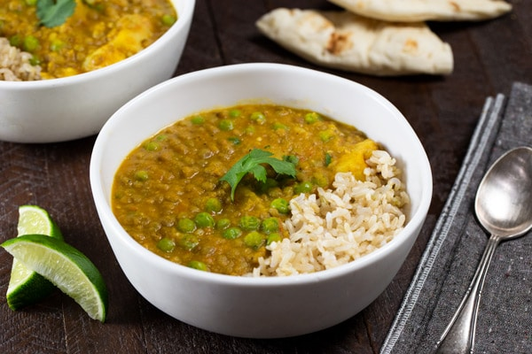Creamy brown lentils in bowl with brown rice and a sprig of cilantro