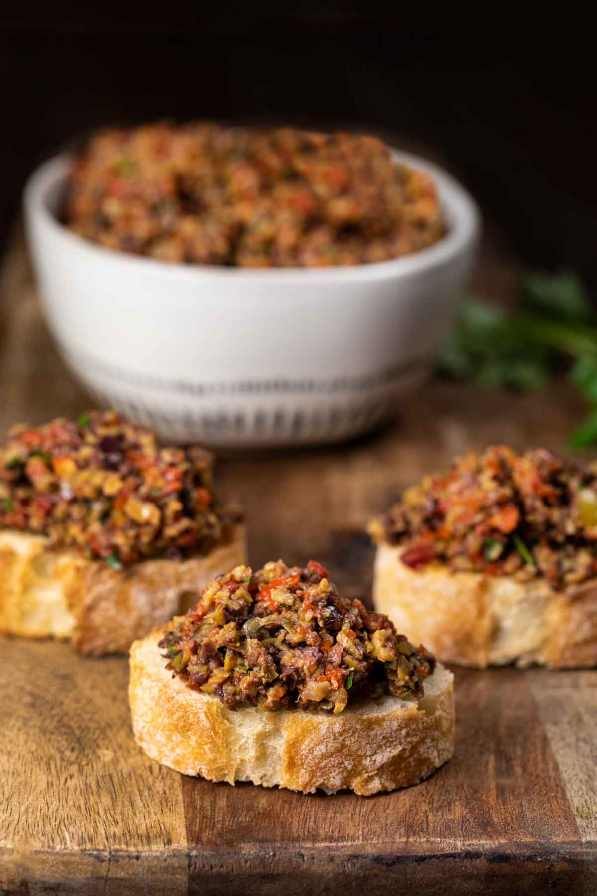 3 pieces of French bread with olive tapenade spread on top.