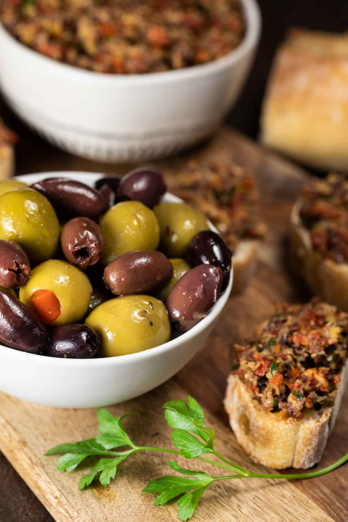 A bowl of olives with crusty bread topped with tapenade.