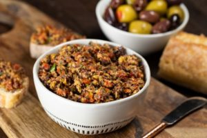 a bowl of olive tapenade with Olive Tapenade spread on slices of French bread