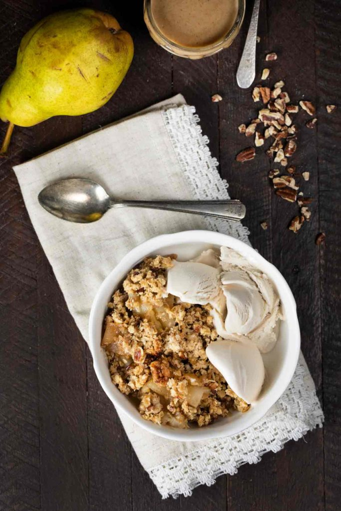 Overhead view of a bowl of pear crisp and ice cream with a spoon.