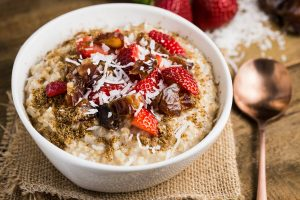 A white bowl filled with instant pot oat meal with fruits sprinkled on top and spoon and strawberries on the side.