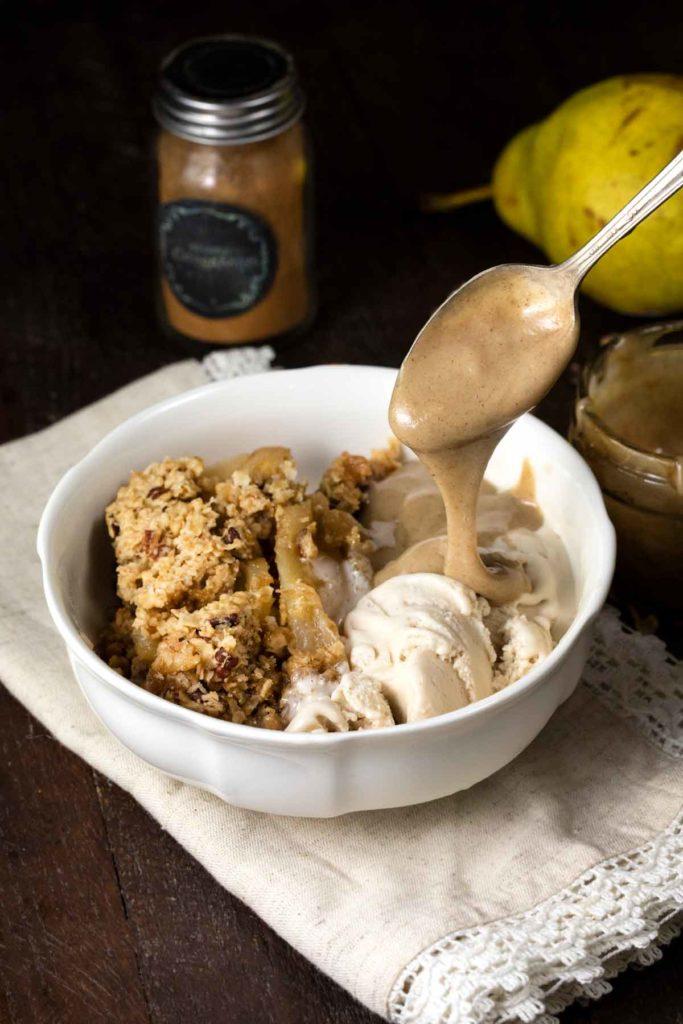 Vegan caramel being drizzled onto pear crisp and vanilla ice cream.