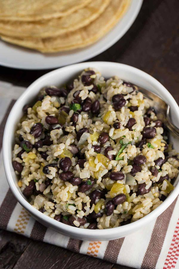 Black beans and rice with green chiles in a white bowl