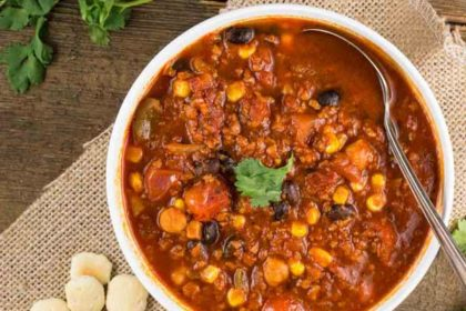 Slow Cooker Soy Chorizo Chili is a white bowl with crackers on the side.