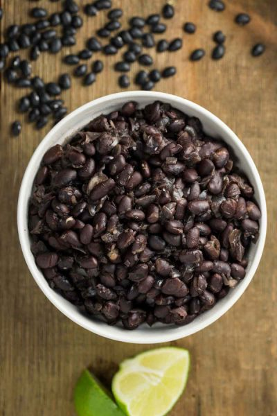 A bowl of instant pot black beans with lime and black beans on the side