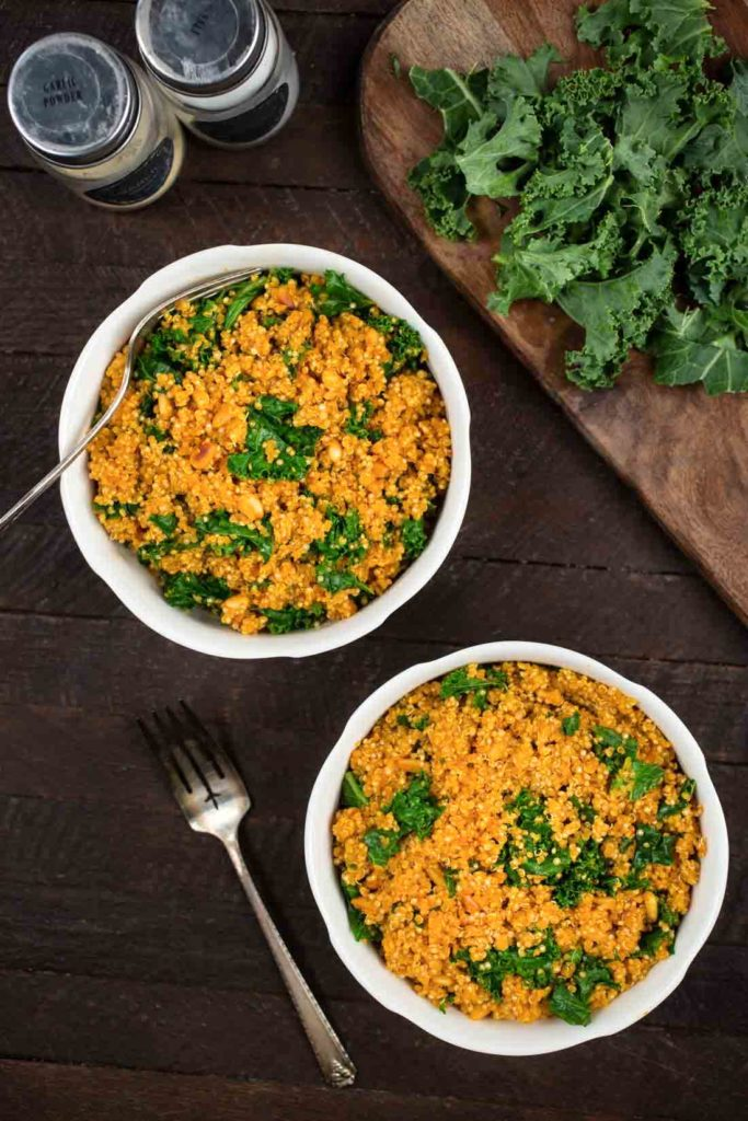 An overhead photo of 2 bowls of Kale Quinoa on a wood background.