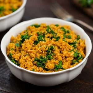 A bowl of quinoa with kale and pine nuts in a white bowl.
