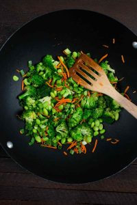 Broccoli and carrots being cooked in a wok