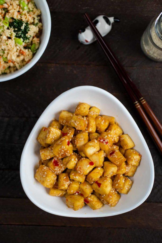 Crispy Sesame Tofu in a white bowl with a side of cauliflower stir fry