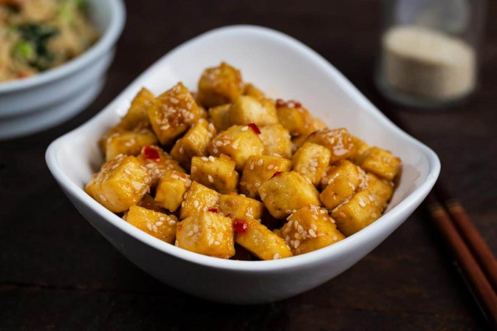 A white bowl filled with crispy sesame tofu.