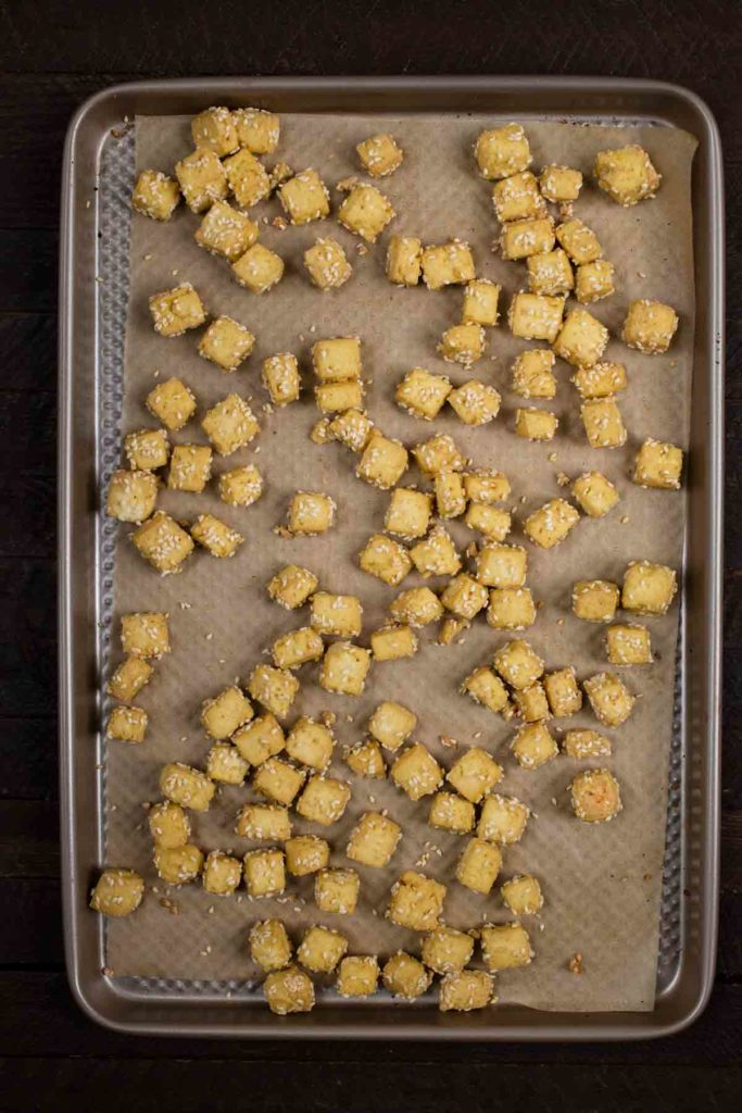 A baking sheet covered with diced tofu.