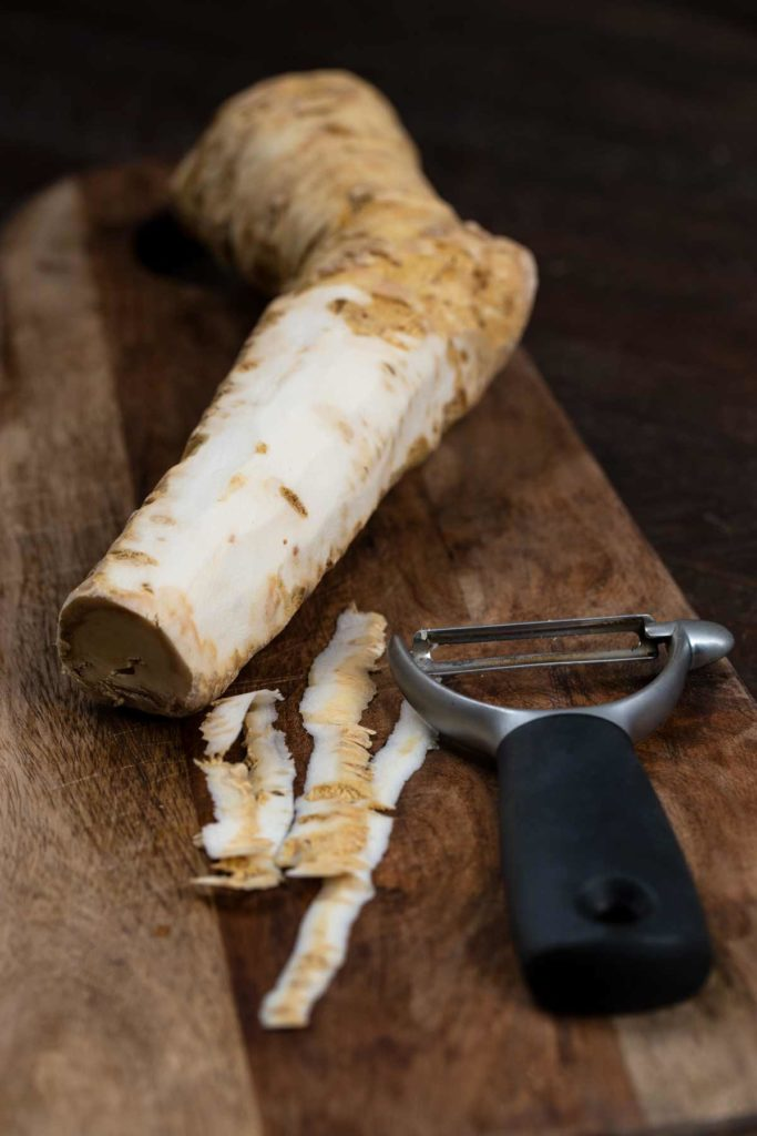 A horseradish being peeled on a cutting board.