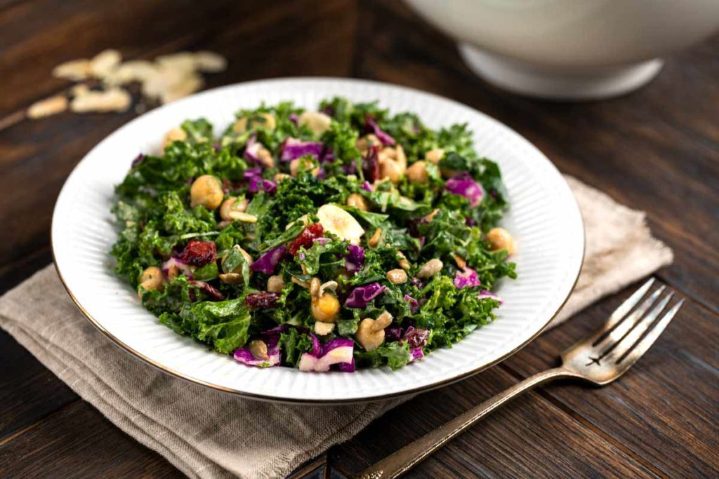 A bowl of kale cranberry salad on a wood backdrop