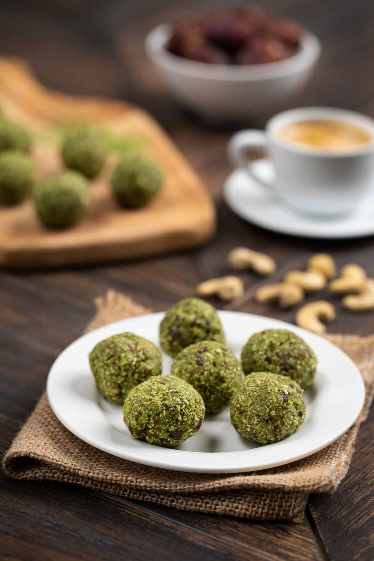 Green tea energy balls on a white plate and a cup of espresso and a cutting board in the background.