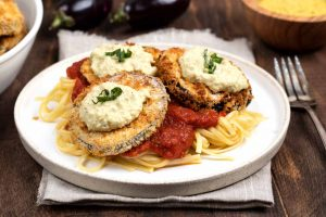 A white plate filled with noodles, marinara and topped with 3 pieces of air fryer eggplant.
