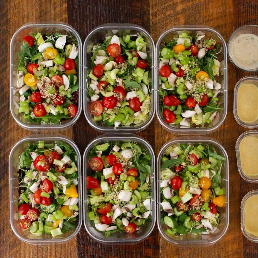 Plastic containers filled with salad and sides of dressing.