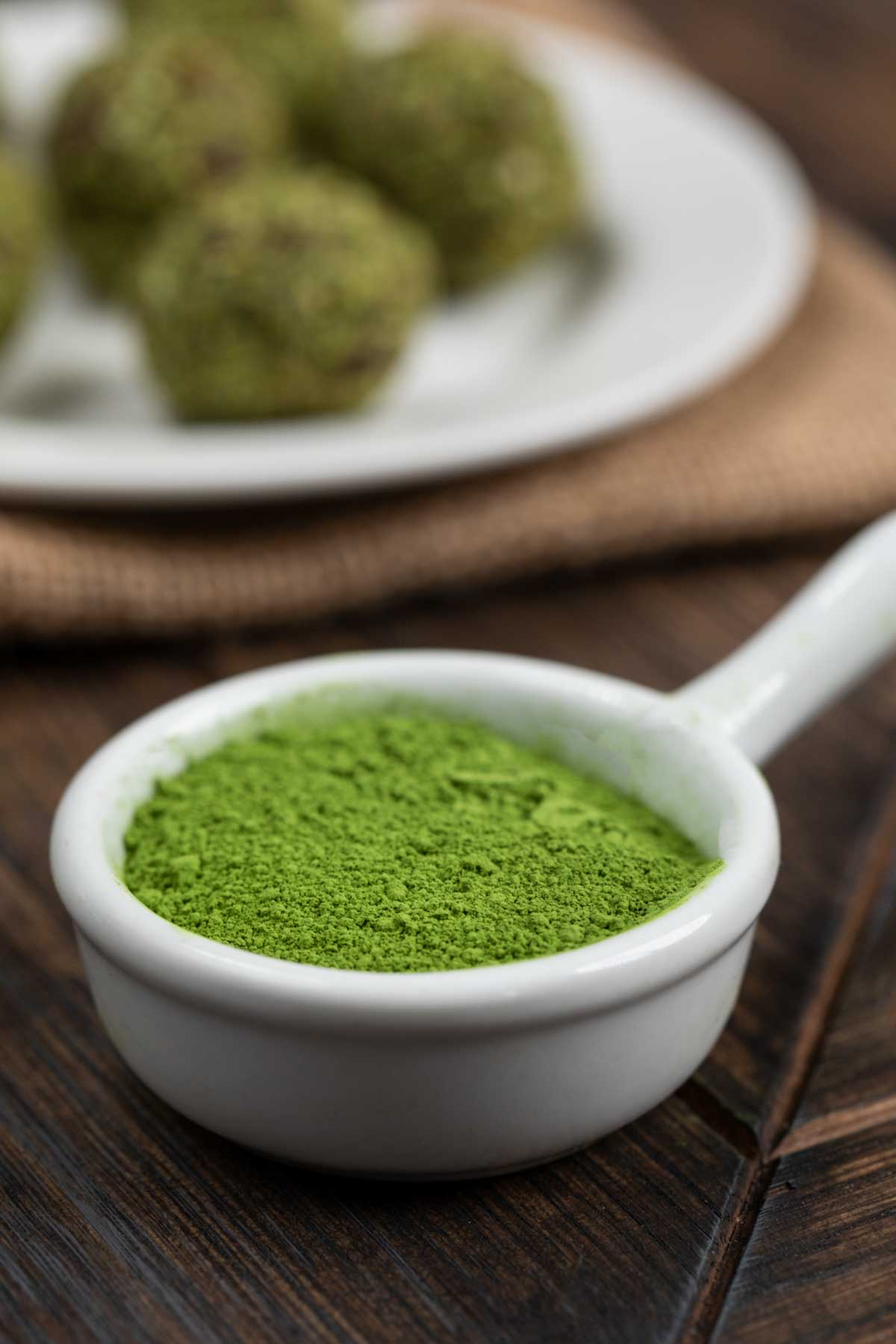 A small white bowl filled with matcha green tea powder, with a plate of energy balls in the background.