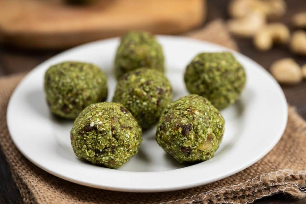 A white plate filled with 6 Matcha Green Tea Energy Balls.