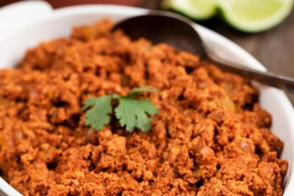 Soy Chorizo Meat in a white bowl with tortillas and limes in the background.