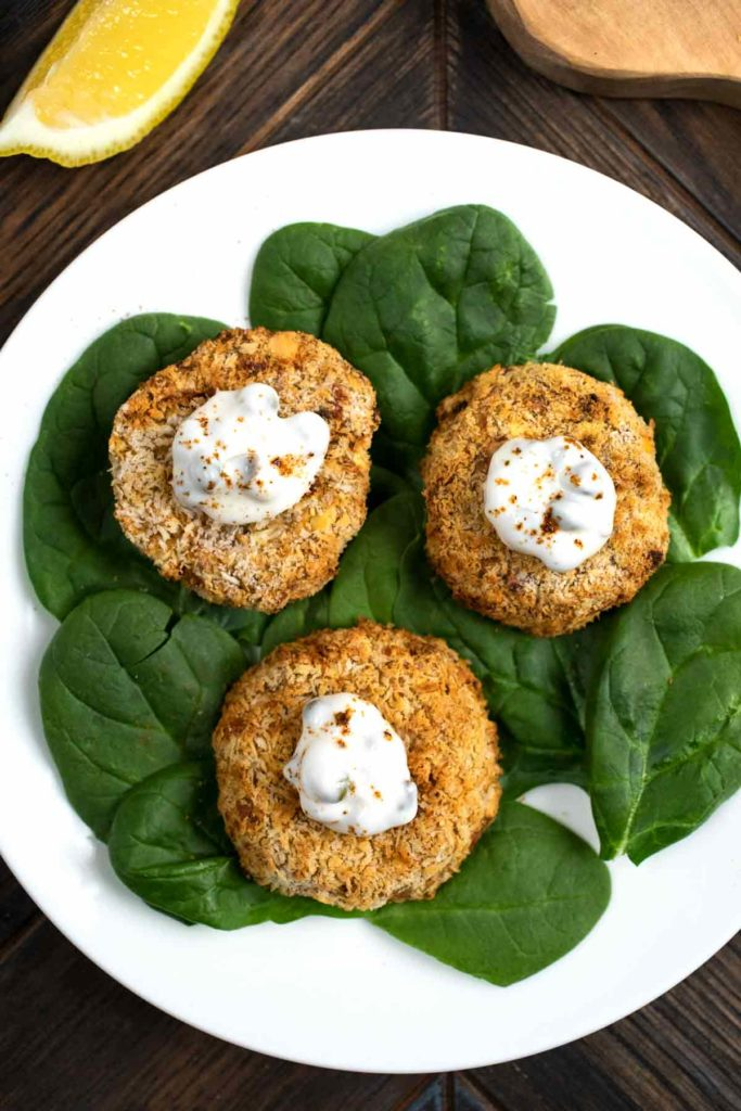 A bird's eye view of a plate of vegan crab cakes on a bed of lettuce.
