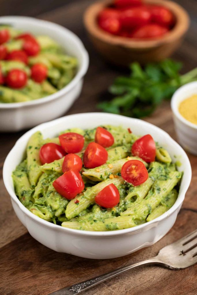 A white bowl filled with avocado pasta topped with cherry tomatoes.