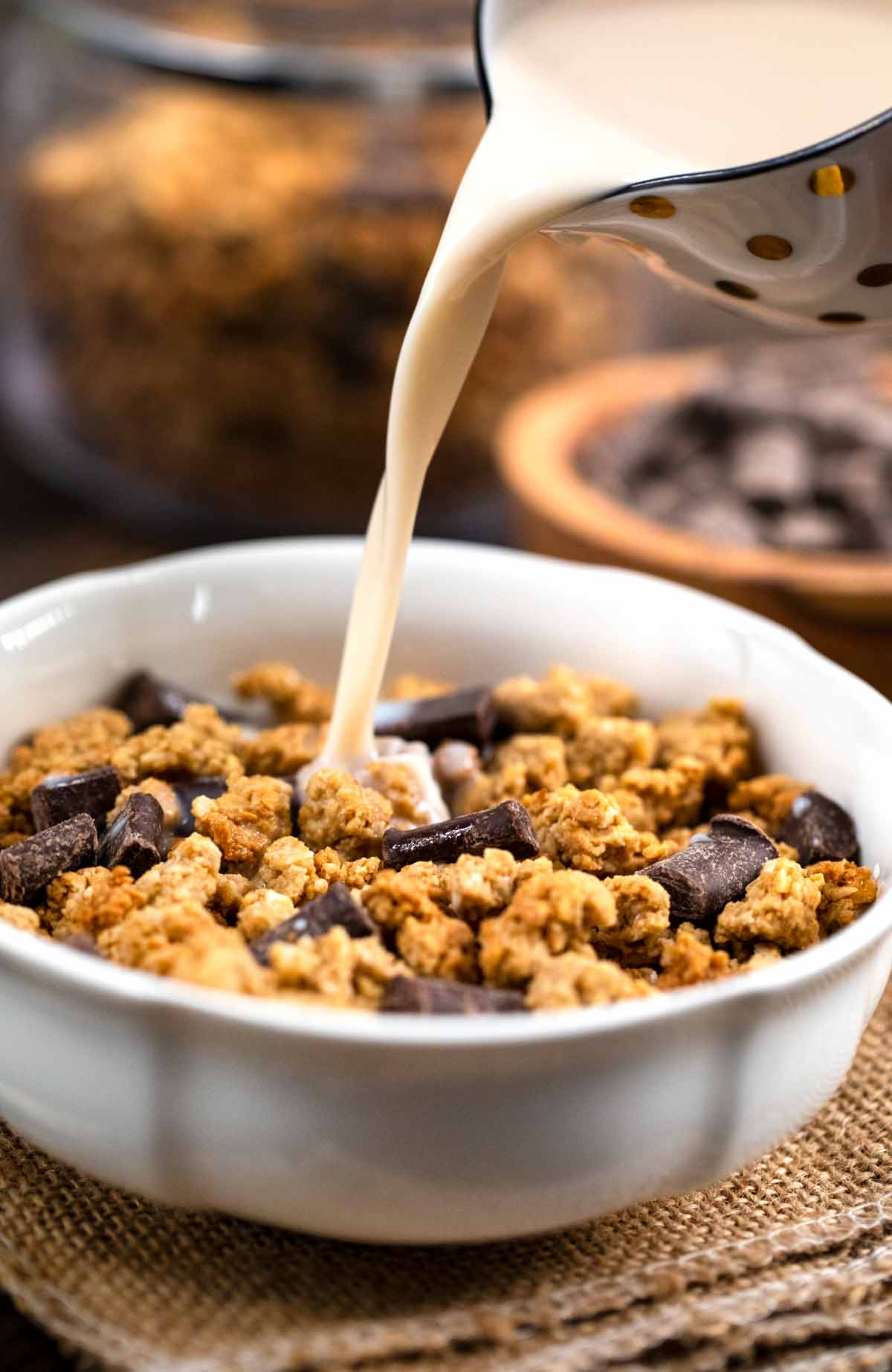 A white bowl filled with baked granola with milk being poured on top.