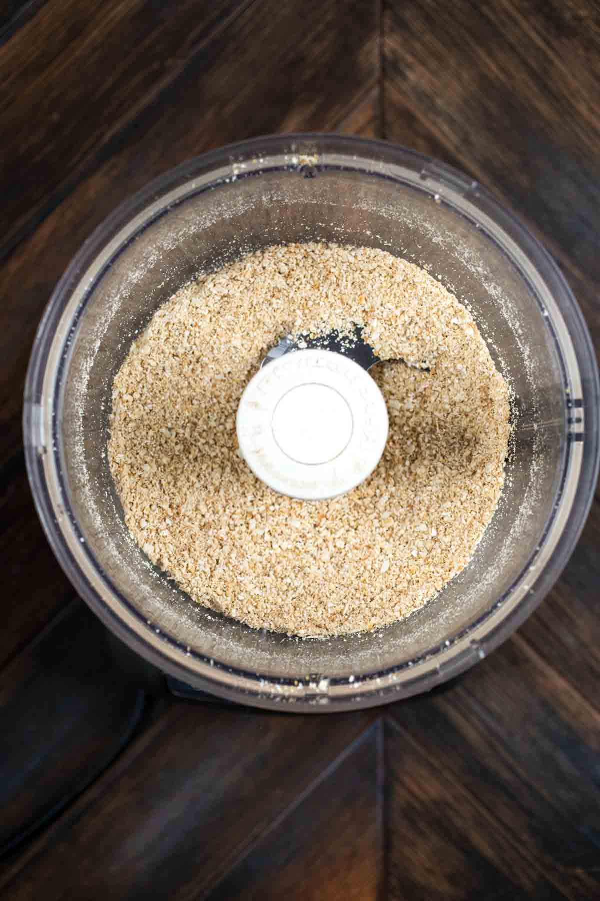 A food processor filled with oatmeal, flax egg, and coconut flakes, mixed together.