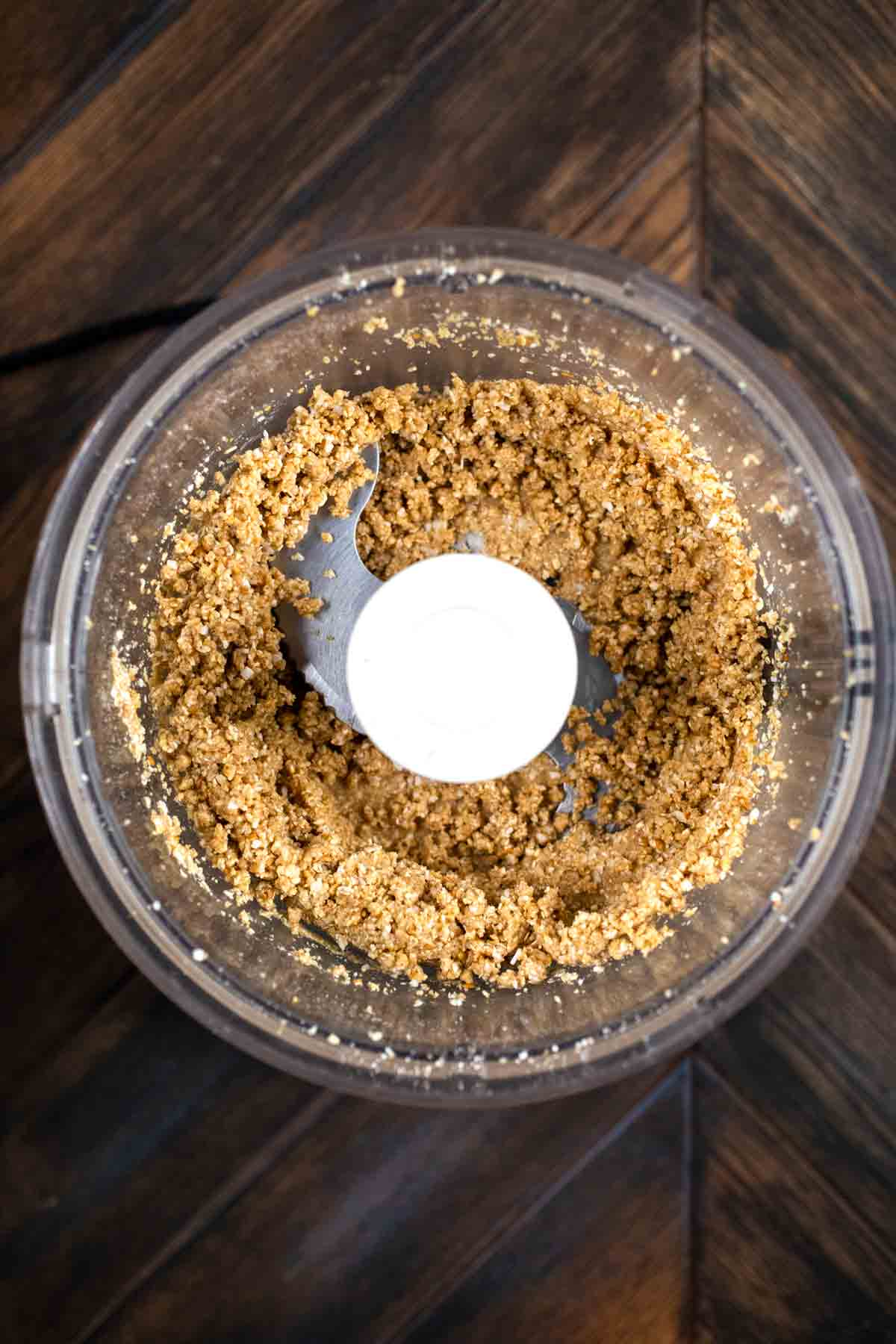A food processor with a baked granola mixture.