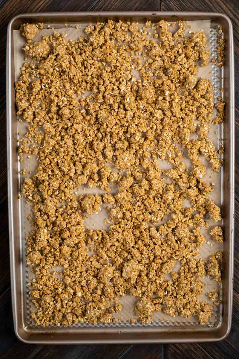 A baking sheet covered in parchment paper and homemade granola.