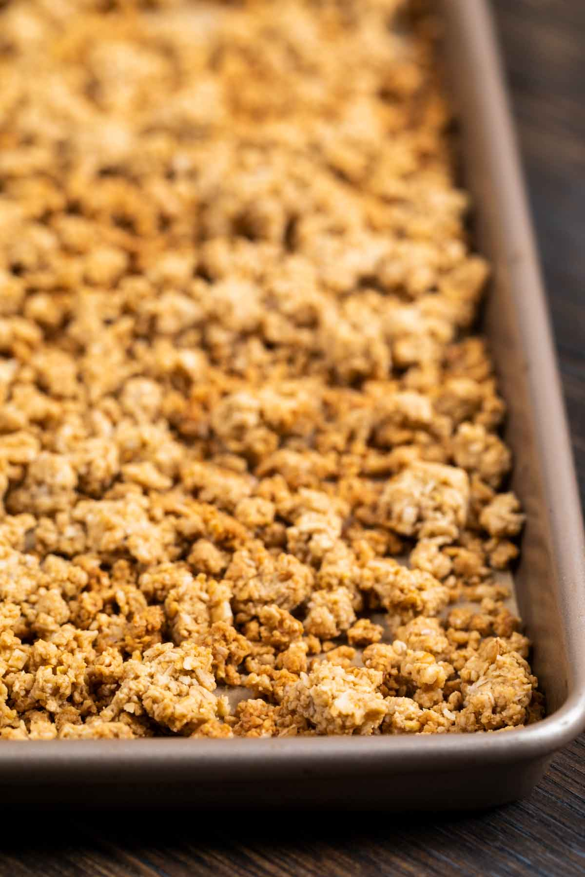 A baking sheet after coming out of the oven, with golden baked homemade granola.