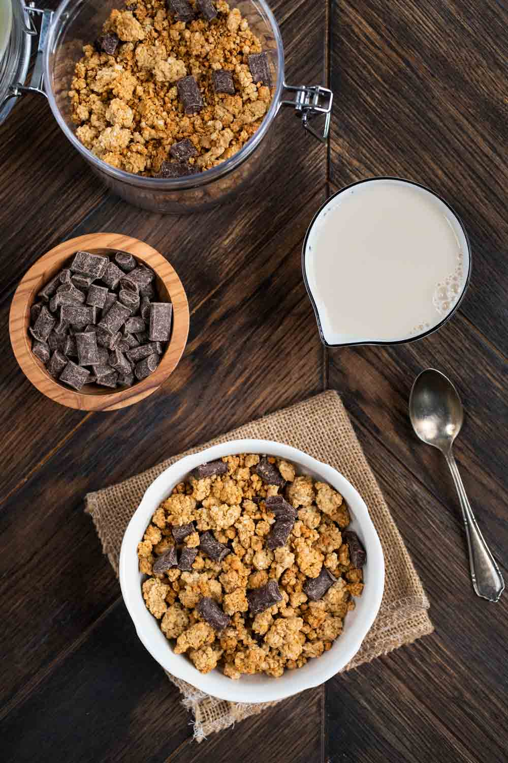 An overhead shot of a bowl of easy baked granola, a cup of milk, a spoon, and additional chocolate chunks in a small bowl.