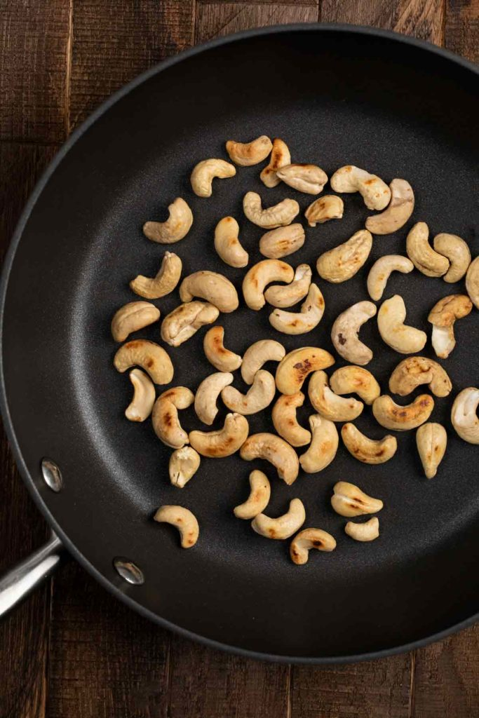 A skillet filled with roasted cashews.