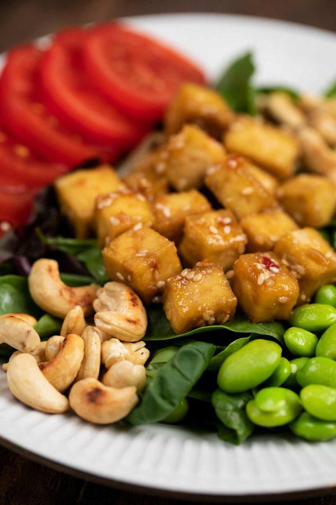 A closeup of a plate of Crispy Sesame Tofu Salad w/ Miso Dressing .
