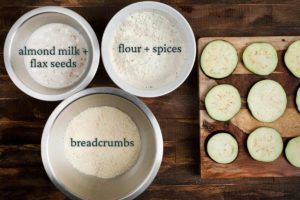3 bowls showing the 3 stations of making air fryer eggplant- almond milk, flour and breadcrumbs.