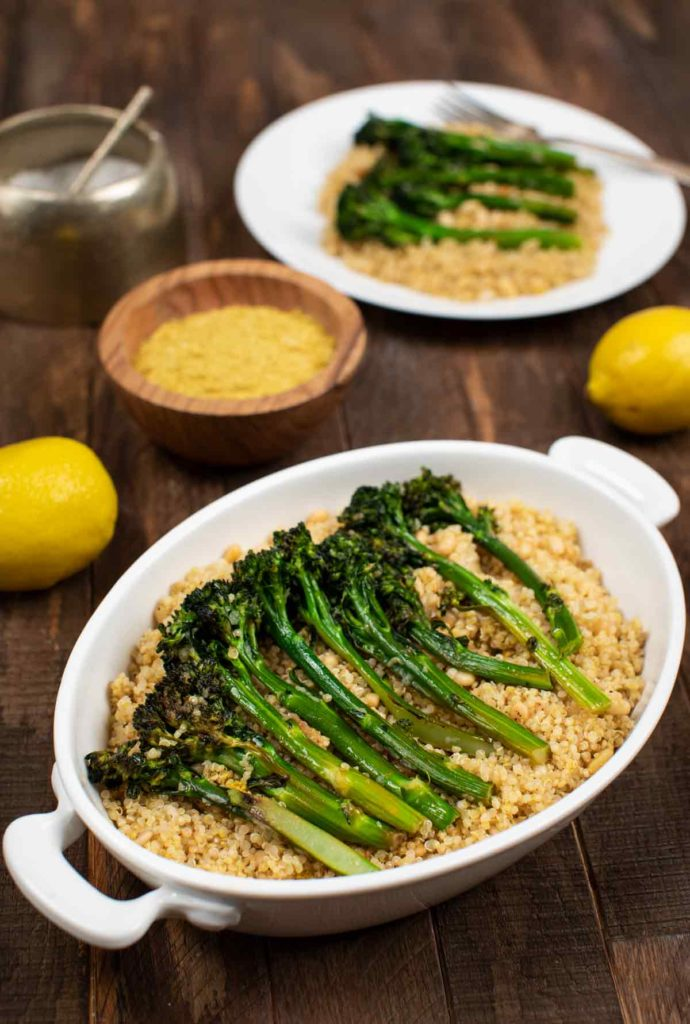 A casserole dish filled with Charred Broccolini layered on top of quinoa.